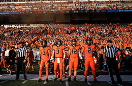 OSU Beaver Football players lined up in a row on the sideline