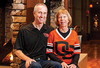 McGrath couple sitting together with their OSU Beaver fan gear